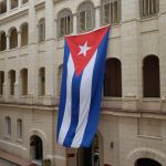 Two-story tall Cuban flag hanging on the side of a building