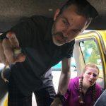 A man holding a frog inside a van