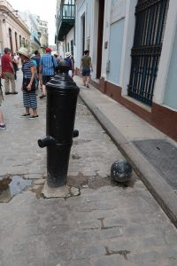 A cannonball and an upside-down cannon that have been cemented into the brick street