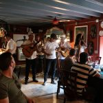 A 5-person band plays music for an audience at a restaurant