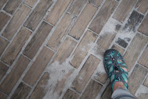 A gray and teal shoe standing on a street of wooden bricks