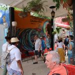 A man walking in a busy alleyway in front of a mural and a painted Cuban flag