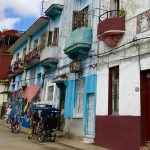 Street of brightly colored buildings - teal, blue, and red, with a bicycle and pedicab parked in front
