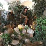 Life-size figures of Che Guevara and Fidel Castro in a diorama with rocks, trees, and greenery
