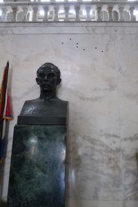Bust of José Martí beside a flag and in front of a marble wall containing bullet holes