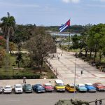 A view of a Cuban street scene with a large Cuban flag and a line of parked classic cars