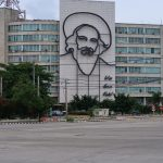 "Building with a metal outline image of Camilo Cienfuegos on it and the words ""Vas bien Fidel."""