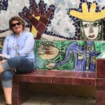 A woman in sunglasses sitting on an illustrated bench with a wall of tile mosaic behind her