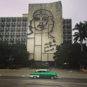 """Building with a metal outline image of Che Guevara on it and the words """"Hasta la victoria siempre."""" A green and white classic car drives by in the foreground"""