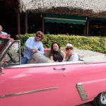 Three women in a pink classic convertible car
