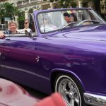 Two women looking out of a purple classic car convertible