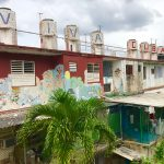 "Eight cylindrical mosaics perched on top of a building. Each one contains a different letter so together they read ""VIVA CUBA"""