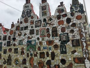 A wall covered in tile mosaic and illustrations