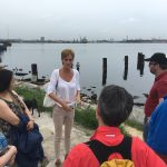 A woman talks to a group of people in front of a body of water