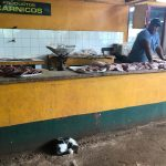 A man stands behind a counter covered in cuts of raw meat. A cat is curled up beneath the counter.