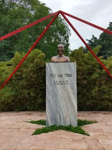 Bust of Ho Chi Minh on a rectangular pedestal with his birth and death dates written on it, beneath 4 red bars that intersect about it