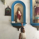 A woman reaches above her to touch the base of a figure of Santa Bárbara