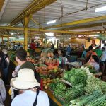 A crowd of people browse the vendor stalls piled with fruits and vegetables