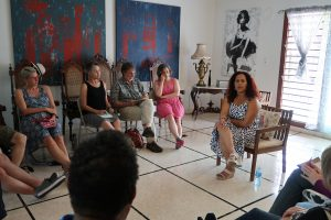 A woman talks to a group of people seated on chairs in a circular formation
