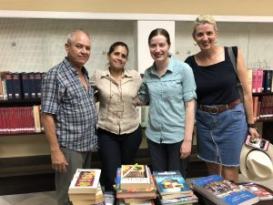 A man and three women stand in front of several stacks of books. Two shelves of books are behind them.