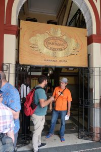 """Two men stand beneath a sign that says """"Flor De Tabacos of Partagas Habana"""""""