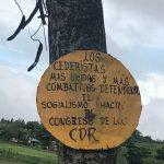 """A yellow circular sign on a tree reading, """"Los Cederistas mas unidos y mas combativos defendiendo el socialismo hacia - Congreso de Los CDR"""