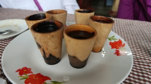 Small cups of coffee in wooden, handle-less cups rest on a white place decorated with red flowers