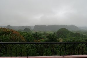 An outlook over a railing - limestone hills and green vegetation