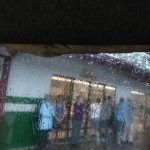 Raindrops slide down a van window through which blurry figures are seen standing under the awning outside a gas station