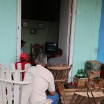 Four men sit in a doorway on wooden chairs watching a TV
