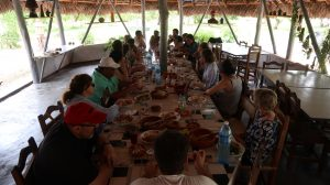 A largue rectangular table full of food and people seated around it under a thatched roof