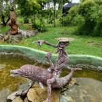 Statute in the middle of a pond of an old, emaciated man riding a fish and wearing a lily pad for a hat