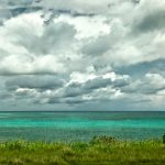Gray and white clouds hang over turquoise water. Green grass is in the foreground.