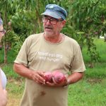 "Farmer Héctor Correa holds three mangoes and is wearing a shirt that says ""foodfirst.org end hunger"""