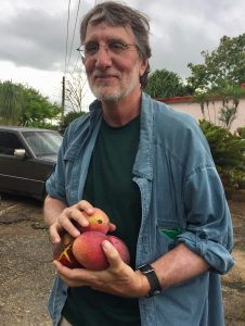 A man standing outdoors holds 4 mangoes in his hands