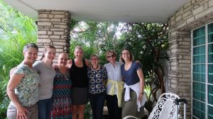 7 women stand on a porch with stone columns