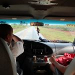 Two men sit in the front seat of a van. Fields line the roadsides.