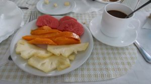 A white plate holding slices of pineapple, mango, and mamey sits next to a saucer holding a cup of coffee