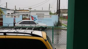 A Cuban flag and a quote from Fidel Castro are painted on the side of a blue wall