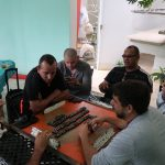 8 people sit around a small, square table containing rows of dominoes