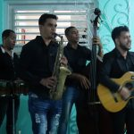 4 men play musical instruments - a guitar, saxophone, bass, and drums