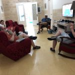 5 people sit in red armchairs looking at their cell phones. A TV plays in the backgound