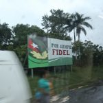 "View from a van window of a sign that reads, ""Por Siempre Fidel"""