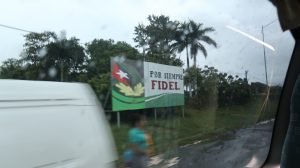 """View from a van window of a sign that reads, """"Por Siempre Fidel"""""""
