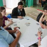 5 people sit around a table with a white tablecloth playing cards