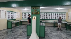 """Black and white photos of men line the walls of a room. A sign on a post in the center of the room reads, """"Heroes de Girón"""""""