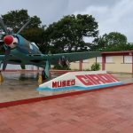 "A plane with gray propellers stands in front of a sign reading: ""Museo Girón"""