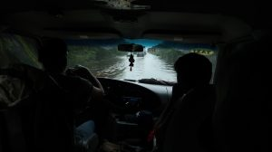 A view out the front van windshield of a water-covered highway