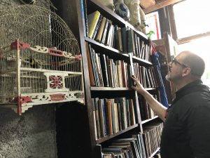 A man looks at shelves of books. A bird in a birdcage hangs in the foreground.