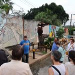 "A man in a blue shirt that says, ""Cuba"" stands in front of a mural and two metal sculpures, talking to a group"